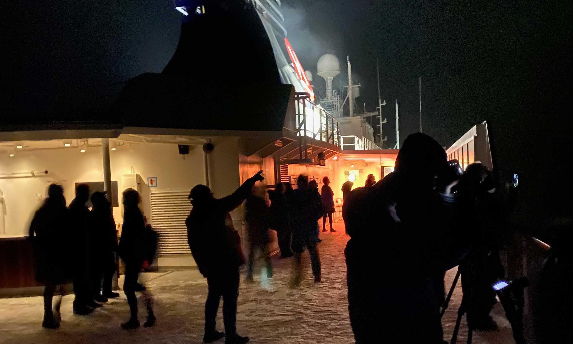 Das Bild zeigt Personen auf der MS Nordnorge, die Polarlichter beobachten