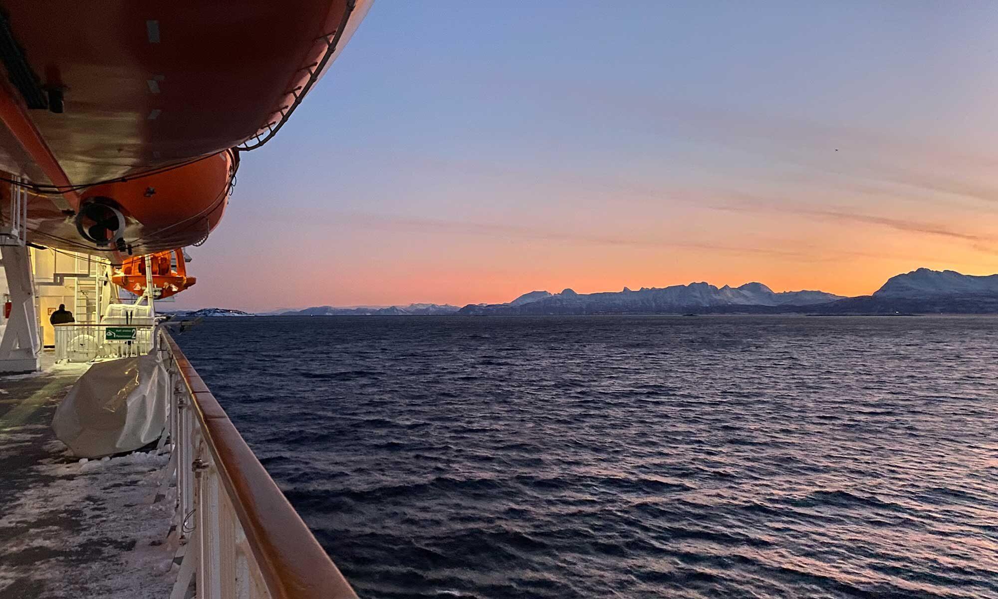 Das Bild zeit einen Sonnenaufgang, Blich vom Schiff MS Nordnorge