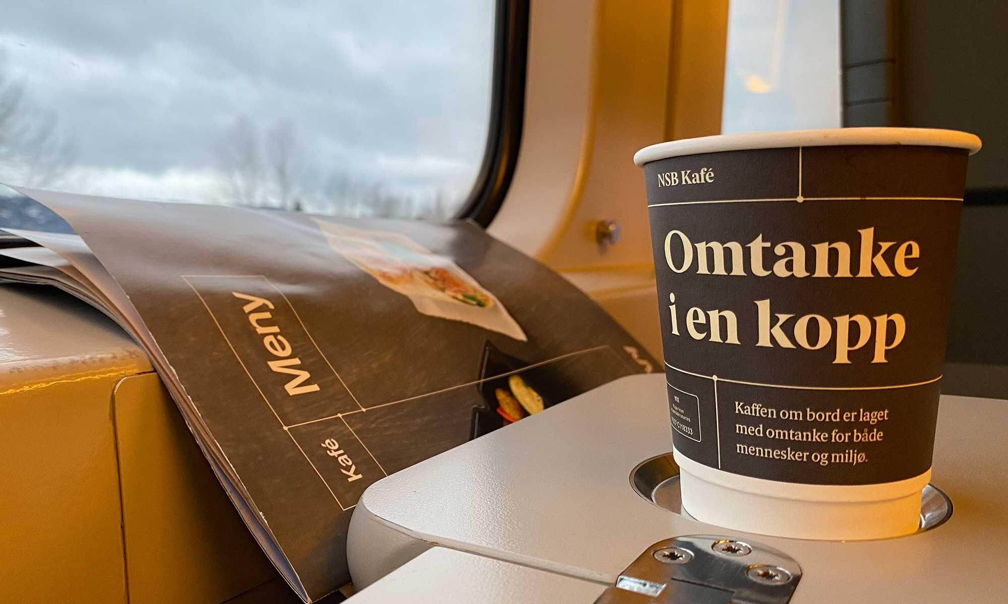 """Das Bild zeigt einen Pappbecher in der Bergenbahn """"omtanke i en kkopp"""""""