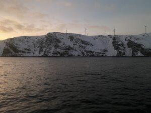 Ausblick von der MS Nordnorge auf das Meer und Küste Windkraftwerk